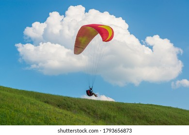 2017-06-25, Kyiv, Ukraine. Red paraglider wing silhouette in the sky with clouds