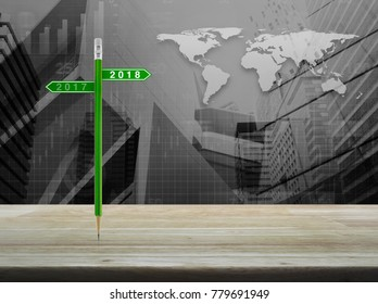 2018 and 2017 direction sign plate with green pencil on table over world map with financial graph and city tower, Business happy new year planning concept, Elements of this image furnished by NASA