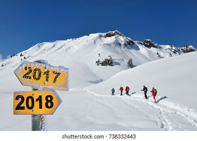 2018 and 2017 written on direction sign in the snow with hikers