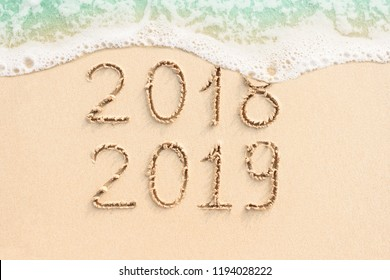 2018 and 2019 handwritten on the sandy beach with soft ocean wave. New Year concept photo.