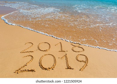 2018 2019 inscription written in the wet yellow beach sand being washed with ocean water wave. Concept of celebrating the New Year at some exotic place.
