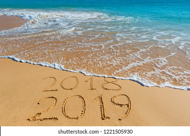 2018 2019 inscription written in the wet yellow beach sand being washed with sea water wave. Concept of celebrating the New Year at some exotic place.