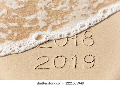 2018 2019 inscription written in the wet yellow beach sand being washed with sea water wave. Concept of celebrating the New Year at some exotic place