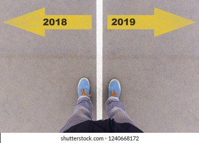 2018 and 2019 text on asphalt ground, feet and shoes on floor, personal perspective footsie concept