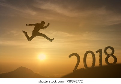 2018 brave man successful concept, silhouette man jumping over the sun between gap of the mountain to 2018 new year, feel like a winner, success, finish, reach a goal of live, jobs, work in year coming