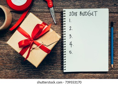 2018 Budget text on notebook paper with gift box.