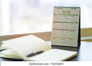 2018 calendar on table in business office with diary, notebook. Planner purpose for business year event, agenda, schedule,planing, booking, appointment, timeline, payment reminder. Calendar concept