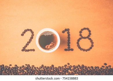2018 coffee beans and a cup of coffee on craft paper in vintage style for new year concept background