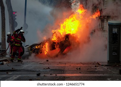2018, December 1th - Paris, France:  Firefighters extenguishing a car on fire during the Yellow Vests protest against Macron politic.