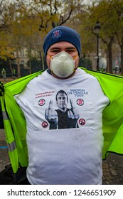 """2018, December 1th - Paris, France:  Yellow vest protester with a tshirt showing Emmanuel Macron with a text """"Macron out"""", """"Macro fuck off"""" during the Yellow Vests protest against Macron politic."""