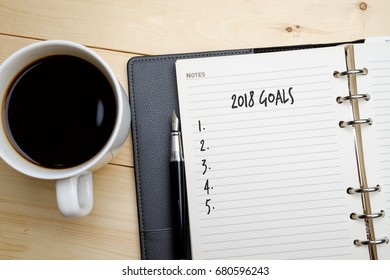 2018 Goals with blank checklist. Note book, pen and a cup of coffee on wooden table.