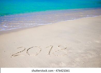 2018 handwritten on sandy beach with soft ocean wave on background