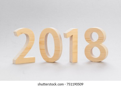 2018 Happy New Year, numbers cut fromlight  wood on a gray background