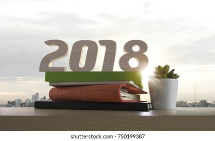 2018 happy new year. Resolutions, goals, start up, refresh concept. Wood numbers, books and plant on wooden tabletop on panoramic skyline and buildings in the morning background.