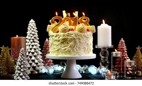 2018 Happy New Year showstopper cake decorated with white chocolate frosting, cookies and candy centerpiece on a festive table.