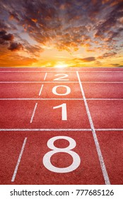 2018 Happy New Year text on athletics sport running track with sunrise sky and clouds