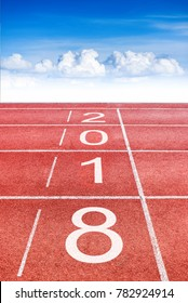 2018 Happy New Year text on athletics sport running track concept with blue sky and clouds