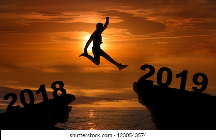 From 2018 into 2019. Silhouette of man jumping between two rocks with numbers, jump into new year concept