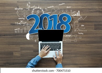 2018 new year business success, Creative thinking drawing charts and graphs strategy plan ideas wooden table background, Inspiration concept with businessman working on laptop computer PC, Top View