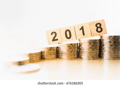 2018 New year and business target concept. Close up of 2018 number wooden block with stack of coins on white background.