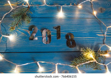 2018 new year and christmas numbers on a blue wooden background and light garland