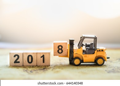 2018 New year concept. Close up of toy forklift truck machine with 2 0 1 8 number wooden block toy on world map.