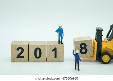 2018 New year concept. Close up of toy forklift truck machine with 2 0 1 8 number wooden blocks toy with workers miniature figures control the working.