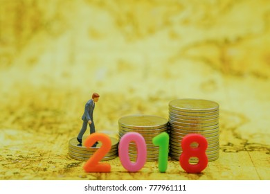 2018 New year Concept. Closeup of businessman minature figure walking on stack of silver coins to the top of chart with colorful plastic number with with map as backgroud.