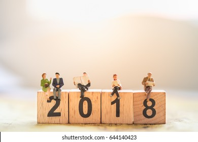 2018 New year concept. Group of businessman and business woman miniature figures sitting on 2 0 1 8 number wooden block toy on world map.