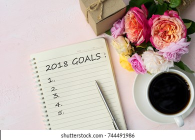 2018 New year goals text on note book with silver pen vintage yellow pink english roses brown gift box and coffee on soft pink wood background with copy space