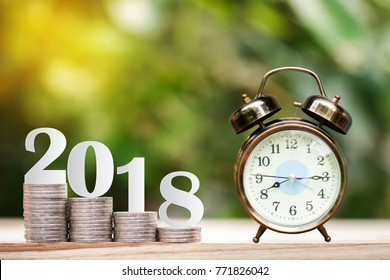 2018 New year on coins stack and clock for saving money and financial planning concept