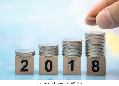 2018 New year and saving concept. Close up of stack of silver coins  on number wooden block with man hand holding and put a coin on top of stack on world map.