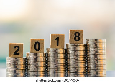 2018 NEW YEAR with stacked coins on wooden block. Business and Financial concept.