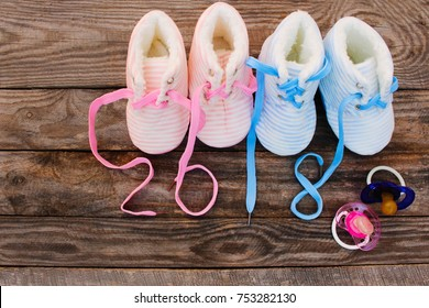 2018 new year written laces of children's shoes and pacifier on old wooden background. Toned image