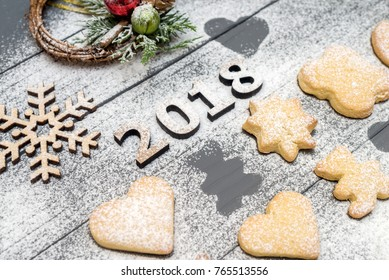 2018 numbers and christmas different shaped cookies with sugar powder and wooden snowflake on wooden table. Top view