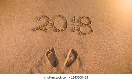 2018 numbers and person's footprints on sea beach sand. Concept of celebrating and traveling on winter holidays.