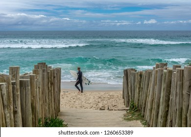 2018, october. Florianopolis, Brazil. Surfer with a board passing in front of a narrow street with the sea at its end. Campeche Beach (Praia do Campeche).