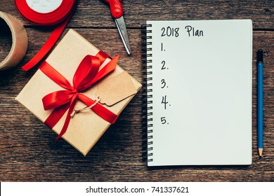 2018 Plan text on notebook paper with gift box for business concept.