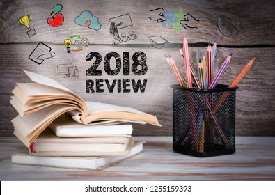 2018 Review concept. Stack of books and pencils on the wooden table.
