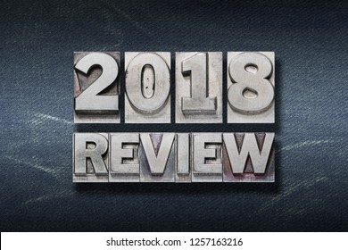 2018 review phrase made from metallic letterpress on dark jeans background