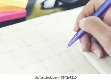 2018 Timetable Event Planner, Close up hand of young Woman holding paper and pen on desk using Calendar for Agenda Management. Calendar Timetable Concept.