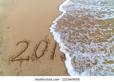 The 2018 written on the sand while the wave is cancelling the 8 symbolising the coming end of the year.
