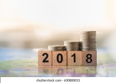 2018 Year and business finance concept. 2 0 1 8 number wooden block toy with stack of coins on world map.
