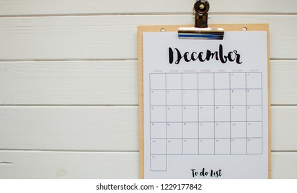 2018 year end review, date planning,  concept on wooden table next to clean calendar on month of December. white background