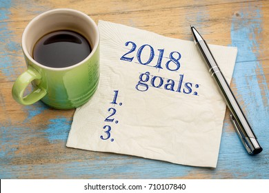 2018 year goals list on a napkin on a wood table with  a cup of coffee