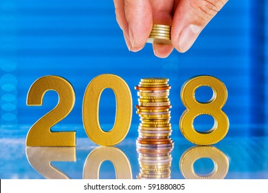 2018 year saving concept,hand push the euro coin in to 2018