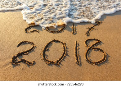 2018 year written on sandy beach sea. Inscription 2017 washes off wave.
