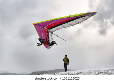 2018-02-25, Kyiv, Ukraine. Brave extreme pilot fly with a hang glider. Dramatic shot with strong wind and snow.
