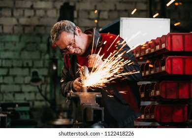 2018-05-21 Russia, Togliatty - Car factory VAZ, Close-up of worker grinding metal with circular saw.