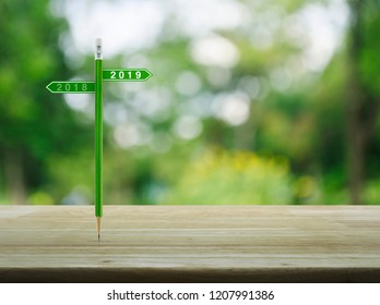 2019 and 2018 direction sign plate with green pencil on wooden table over blur green tree in park, Business happy new year planning concept